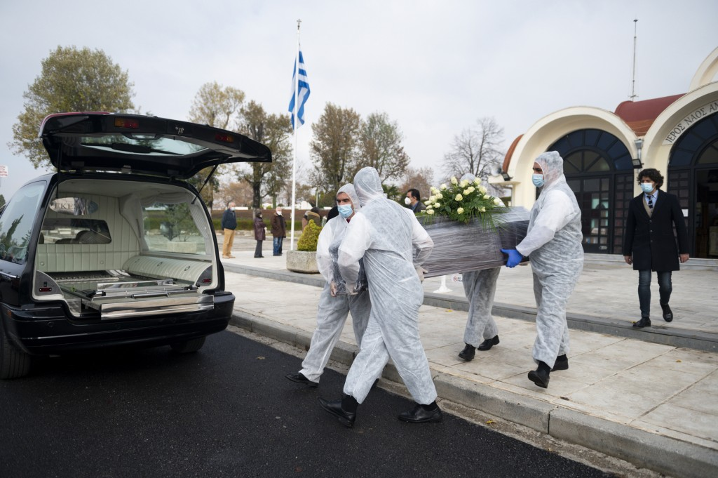 Pallbearers, wearing protective suits and gloves, carry a coffin during a funeral ceremony for a person who died of COVID-19, in the northern city of ...