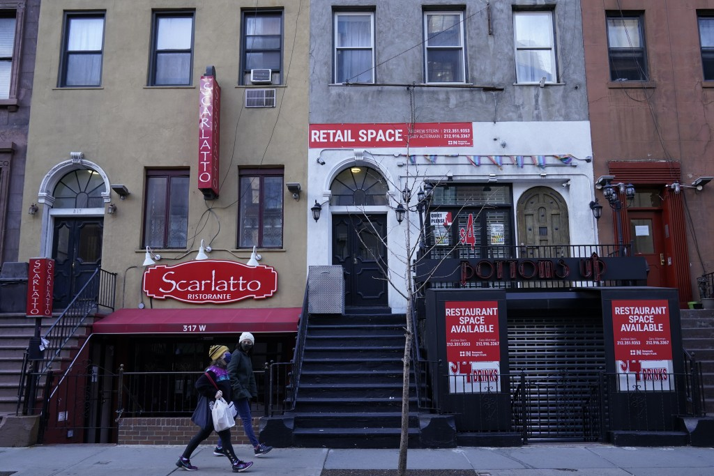 Pedestrians walk past a couple of closed restaurants on Restaurant Row, Sunday, Jan. 10, 2021, in the Hell's Kitchen neighborhood of New York. The boa...
