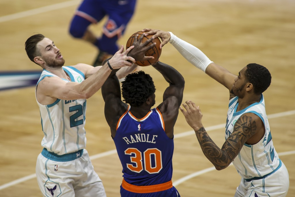 Charlotte Hornets forwards Gordon Hayward, left, and P.J. Washington, right, fight New York Knicks forward Julius Randle (30) for the ball in the firs...