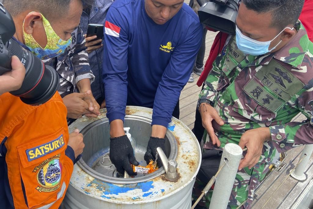 Indonesian navy personnel inspect a part the flight data recorder of Sriwijaya Air flight SJ-182 retrieved from the Java Sea where the passenger jet c...