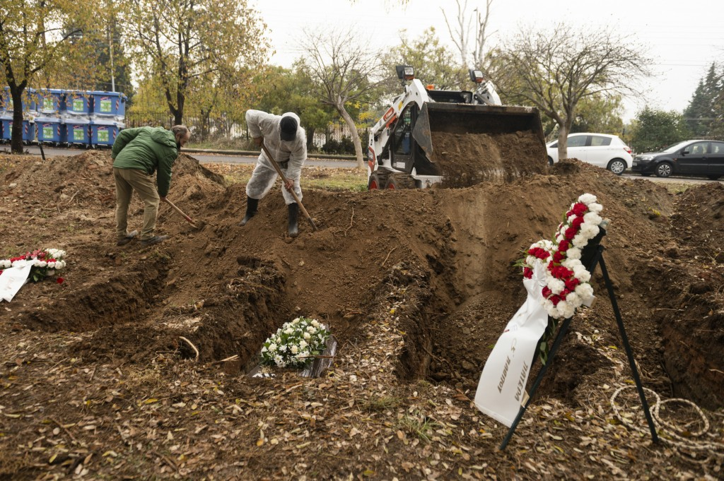 Workers shovel soil over a coffin during a funeral ceremony for a person who died of COVID-19, in the northern city of Thessaloniki, Greece, Saturday,...