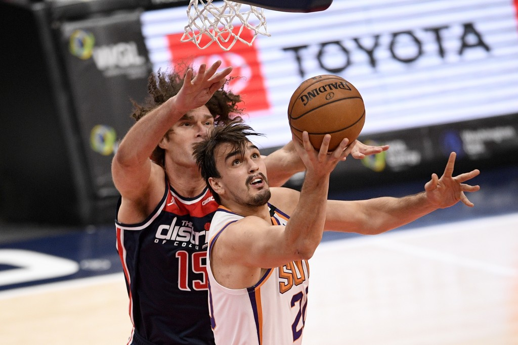 Phoenix Suns forward Dario Saric (20) goes to the basket past Washington Wizards center Robin Lopez (15) during the first half of an NBA basketball ga...