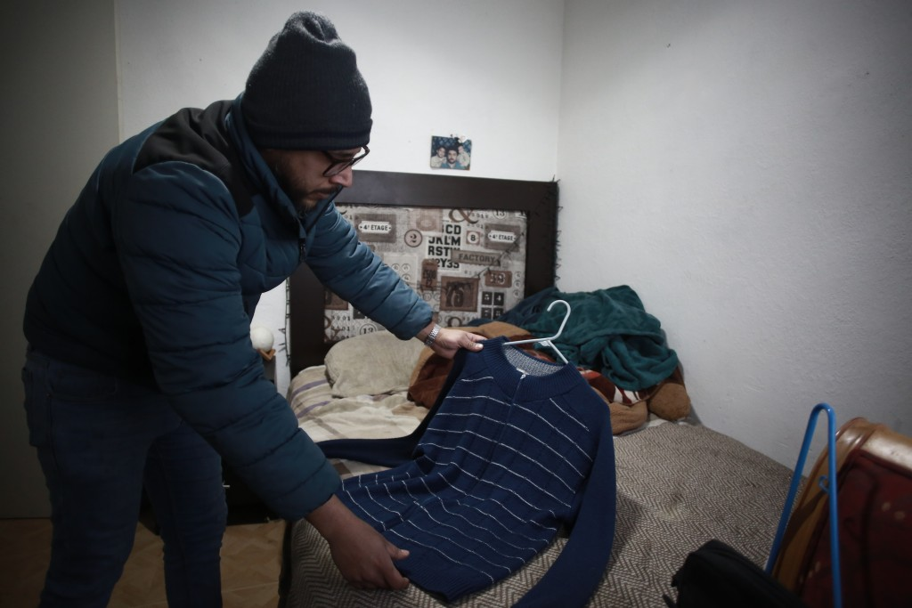Jaime Walfre Aguilar Martinez, whose 50-year-old father died of COVID-19 in November, selects one of his father's favorite sweaters to have a stuffed ...