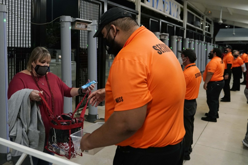A security officer checks a fan arriving for an NCAA College Football Playoff national championship game between Alabama and Ohio State Monday, Jan. 1...