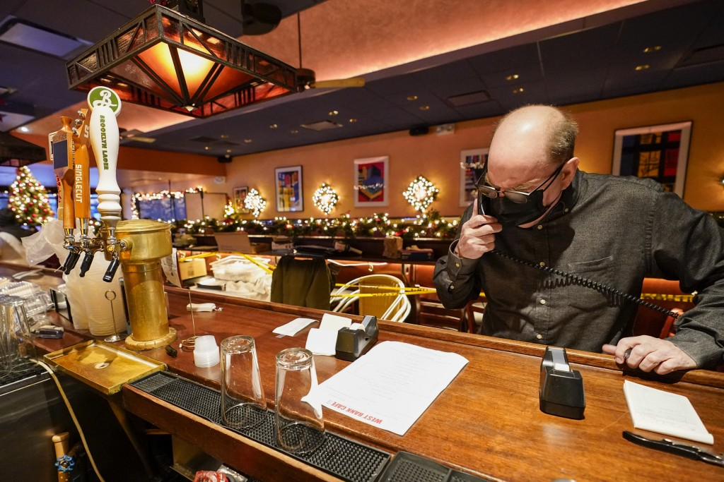 Steve Olsen, the owner of the West Bank Café, reads the specials over the phone to a to-go customer in the empty restaurant, Saturday, Jan. 9, 2021, i...