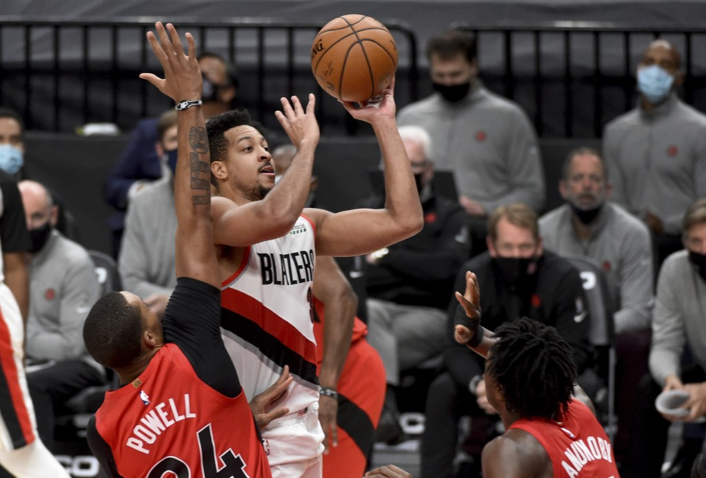 Portland Trail Blazers guard CJ McCollum, center, drives to the basket on Toronto Raptors guard Norman Powell, left, and forward OG Anunoby, right, du...
