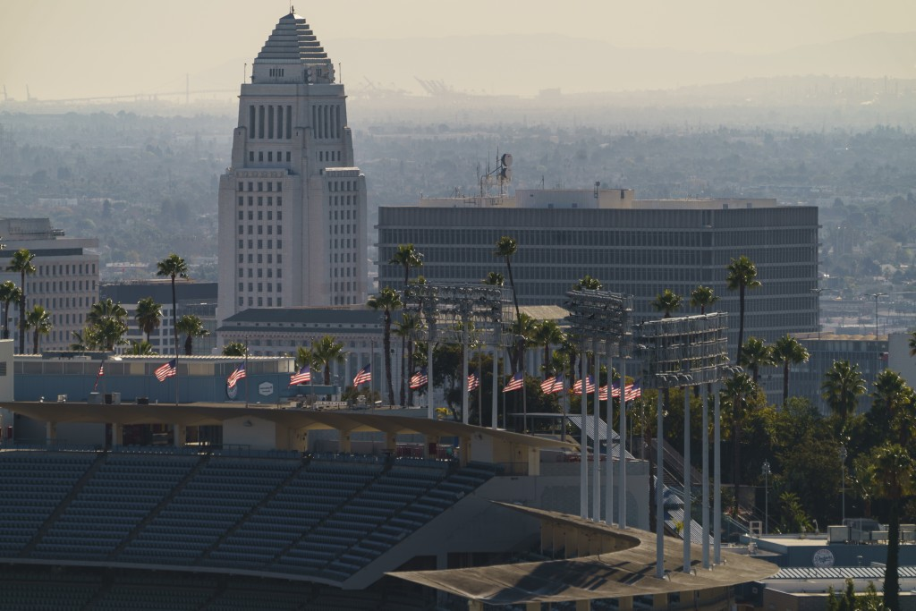 Flags fly half-mast at Dodgers Stadium in honor of the recent passing of the Hall of Fame manager Tommy Lasorda overlooking Los Angeles City Hall Mond...