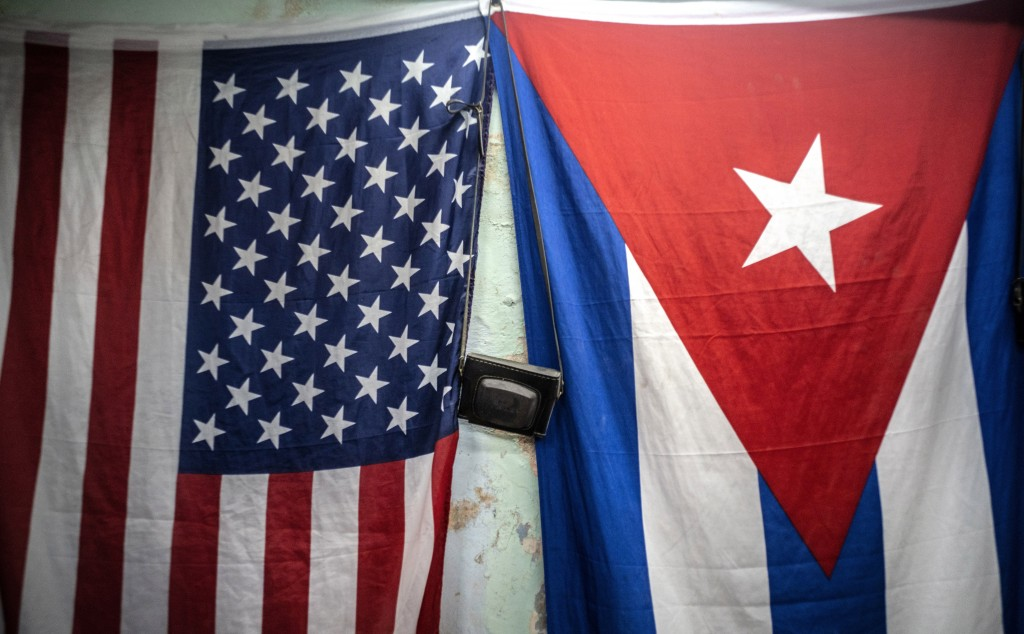 A U.S. and Cuban flags hang from a wall with an old photo camera hung in between in Havana, Cuba, Monday, Jan 11, 2021. The Trump administration has r...