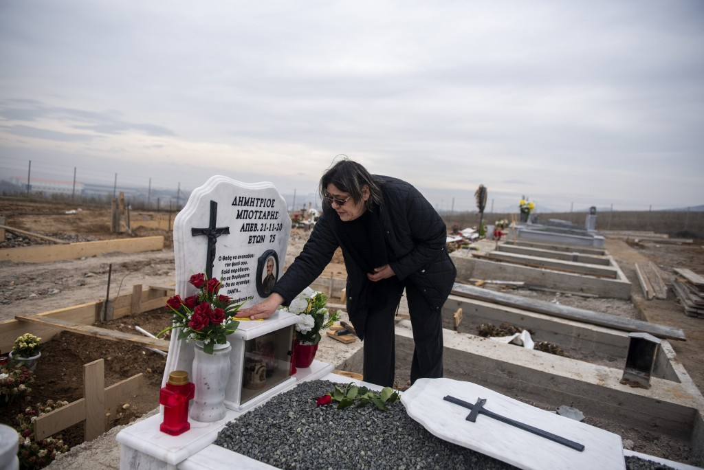 69 year-old Chrisanthi Botsari cleans the grave of her husband in a cemetery set up for victims of COVID-19, at the northern city of Thessaloniki, Gre...