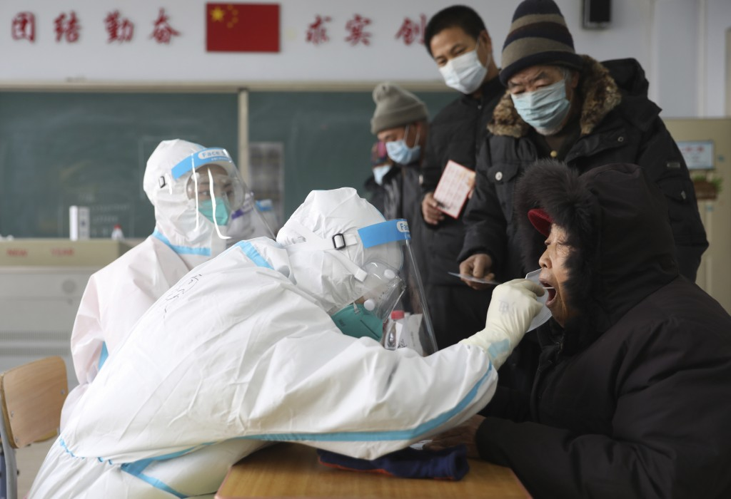 In this photo released by China's Xinhua News Agency, workers in protective suits take a swab for a coronavirus test in Shenyang in northeastern China...