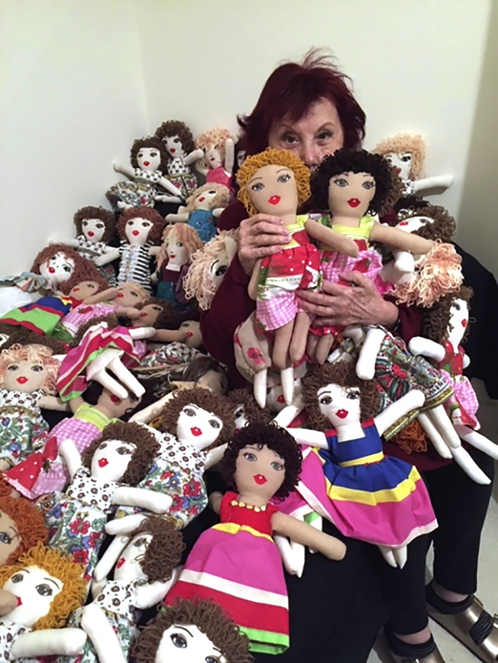 In this photo provided by Lebanese painter Yolande Labaki, Labaki, 93, holds dolls at her house in Beirut, Lebanon, Monday, Nov. 16, 2020, that she ma...