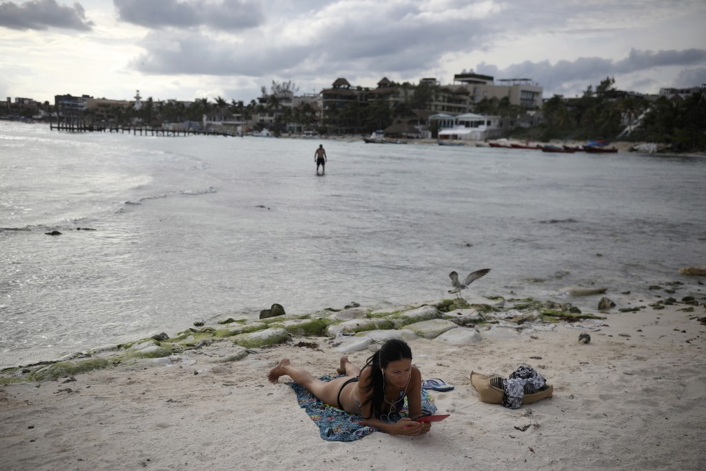 A tourist relaxes on the shore of Mamitas beach amid the new coronavirus pandemic in Playa del Carmen, Quintana Roo state, Mexico, Tuesday, Jan. 5, 20...