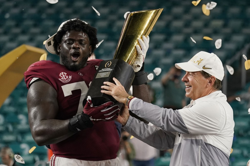 Alabama head coach Nick Saban and offensive lineman Alex Leatherwood hold the trophy after their win against Ohio State in an NCAA College Football Pl...