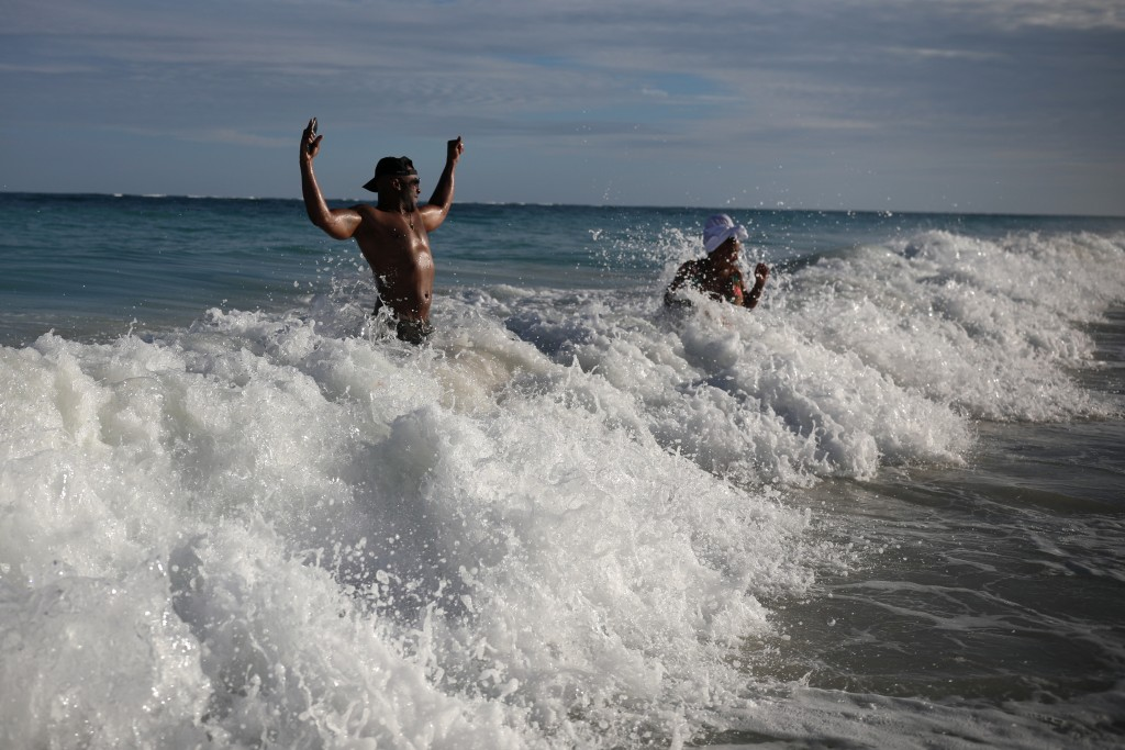 U.S. tourist Latron Evans and his partner Nika, frolicking ocean waters at the beach in Tulum, Quintana Roo state, Mexico, Monday, Jan. 4, 2021. Evans...