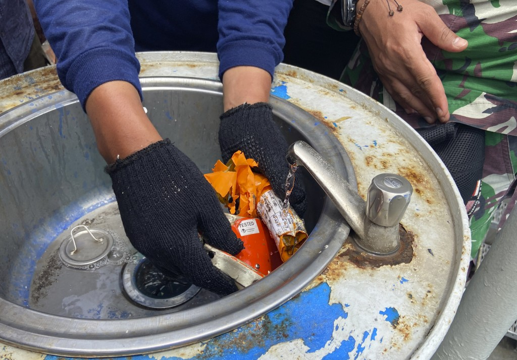 Indonesian navy personnel inspect a part the flight data recorder recovered at the crash site of the Sriwijaya Air flight SJ-182 at the Tanjung Priok ...