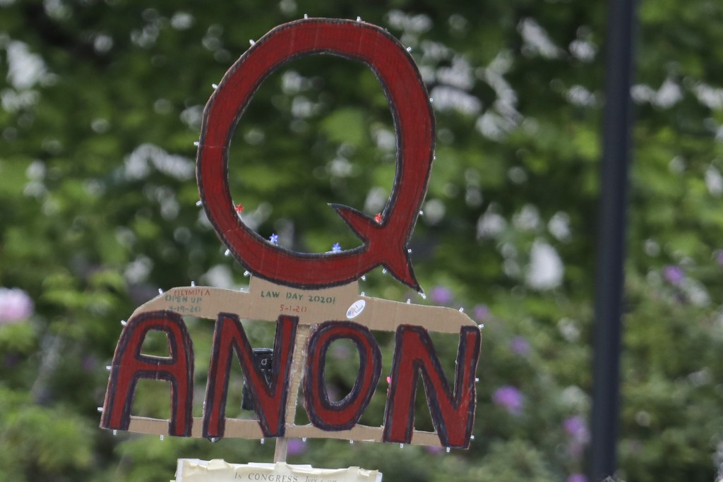 FILE - In this May 14, 2020, file photo, a person carries a sign supporting QAnon during a protest rally in Olympia, Wash, USA.  The social media comp...