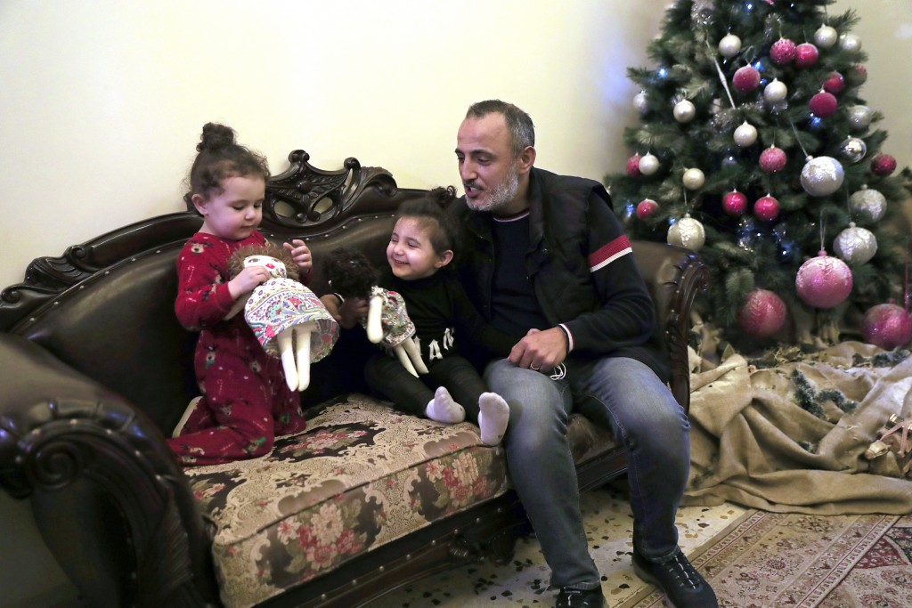 Georges Chlawuit, right, sits with his daughters Sama, 2, left, and Sima-Rita, 3, center, as they play with dolls at a relative's home, in Beirut, Leb...