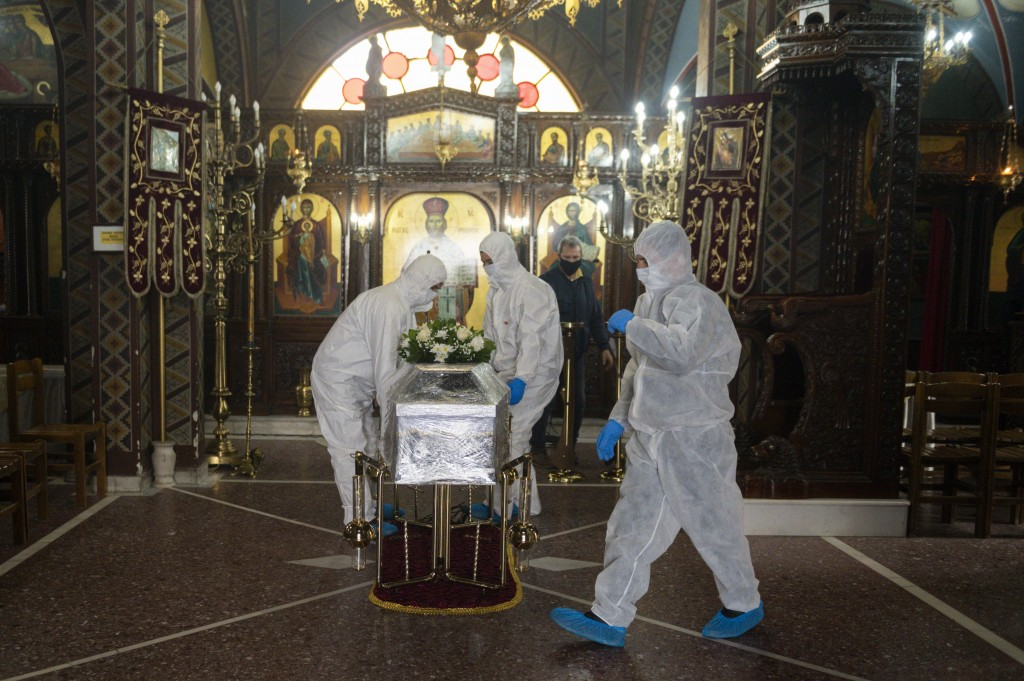 Pallbearers wearing protective suits place a coffin inside an Orthodox church, during a funeral ceremony for a person who died of COVID-19, in the nor...
