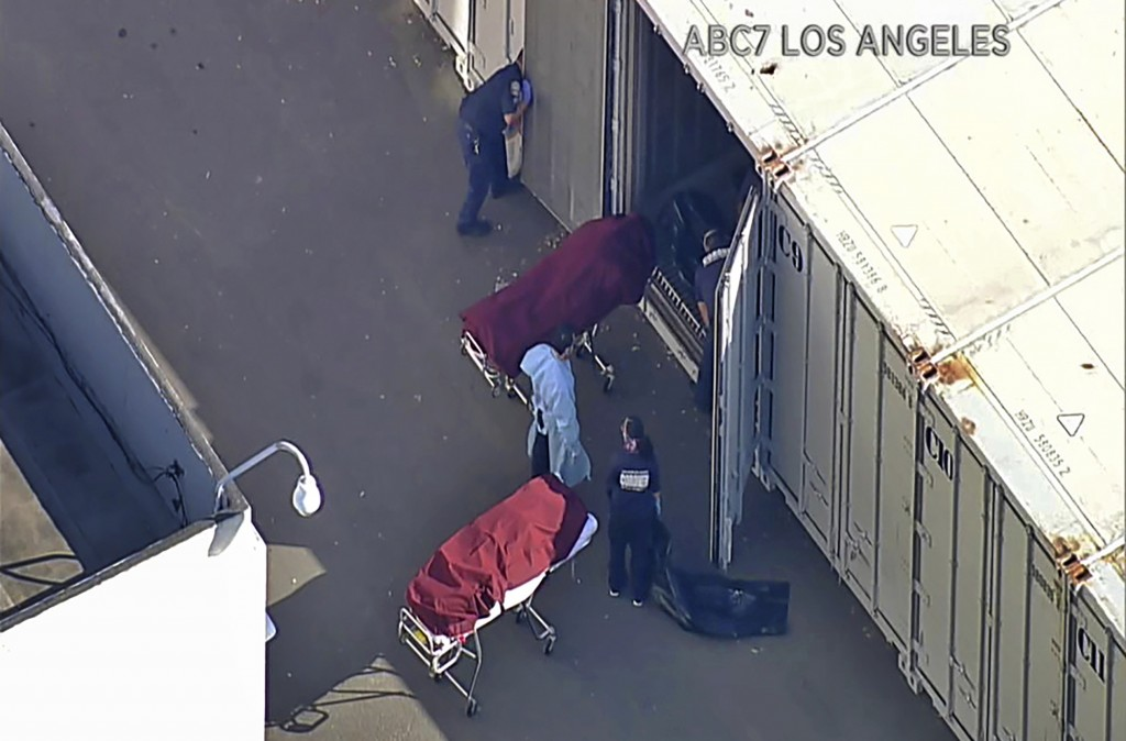 This photo from video provided by ABC7 Los Angeles shows workers putting bodies into a refrigerated trailer at the offices of the Los Angeles County C...
