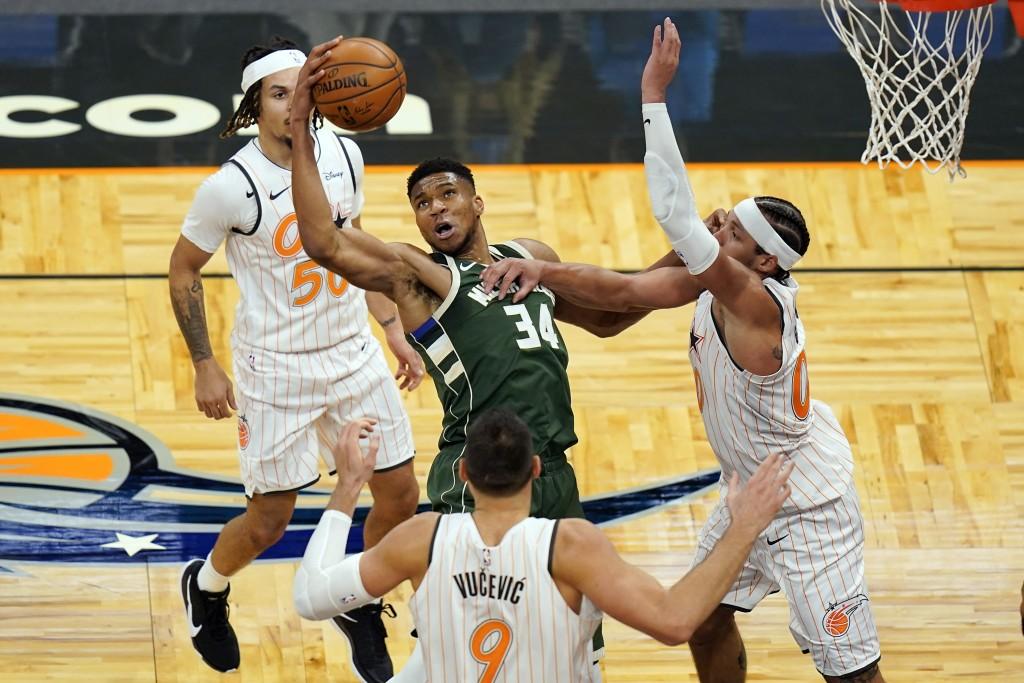 Milwaukee Bucks forward Giannis Antetokounmpo (34) tries to get control of a loose ball between Orlando Magic guard Cole Anthony, bak left, center Nik...