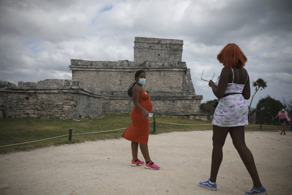 Tourists, required to wear protective face masks amid the new coronavirus pandemic, visit the Mayan ruins of Tulum in Quintana Roo state, Mexico, Tues...
