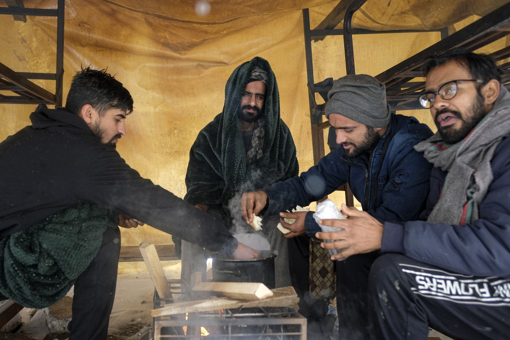 Migrants eat, at the Lipa camp, outside Bihac, Bosnia, Monday, Jan. 11, 2021. Aid workers say migrants staying at a camp in northwestern Bosnia have c...