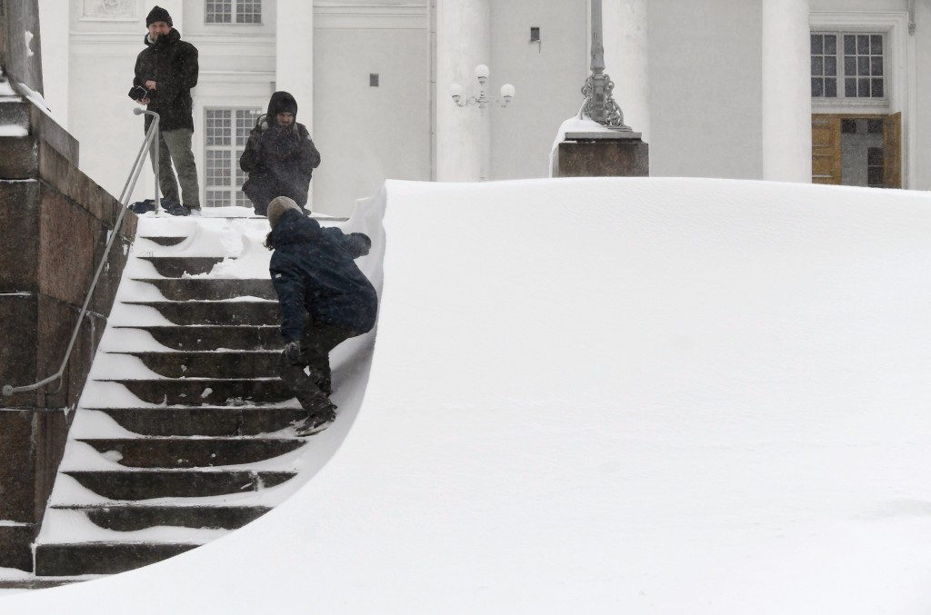 Men take pictures of the snow sweeping across the steps before Helsinki Cathedral during a heavy snow storm making all kinds of travel difficult in He...