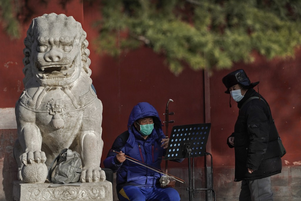 A man wearing a face mask to help curb the spread of the coronavirus watches a masked man play a traditional musical instrument at a public park in Be...