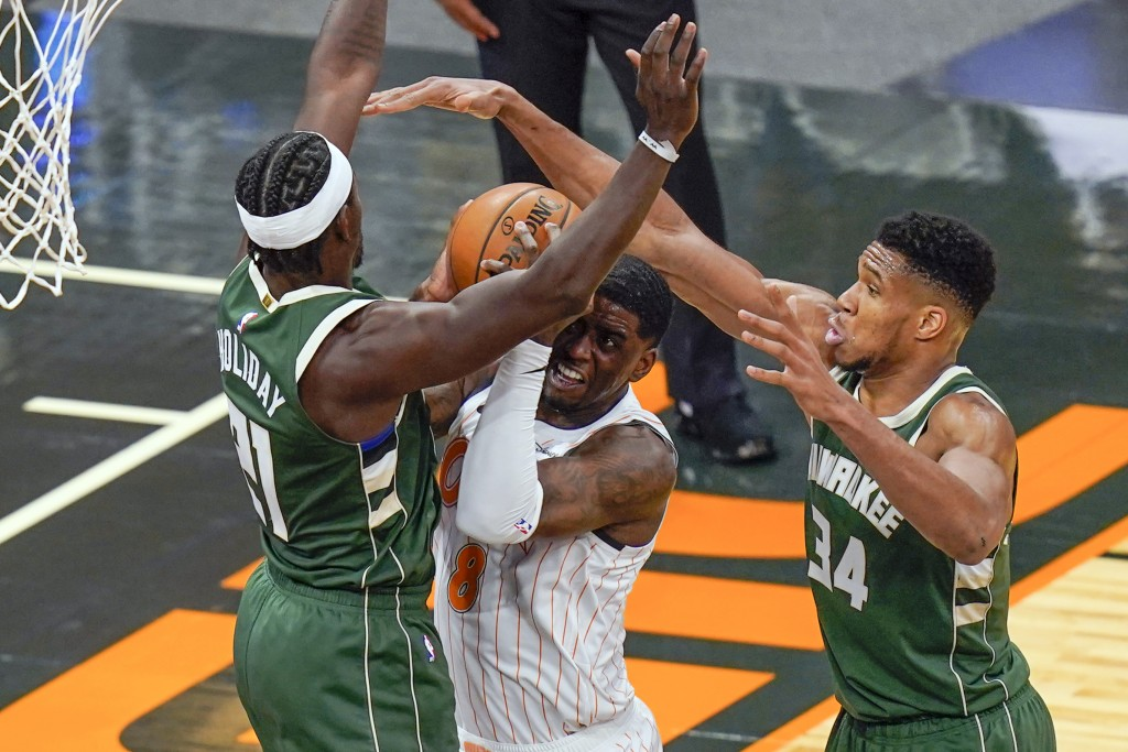Orlando Magic forward Dwayne Bacon, center, tries to get off a shot between Milwaukee Bucks guard Jrue Holiday, left, and forward Giannis Antetokounmp...