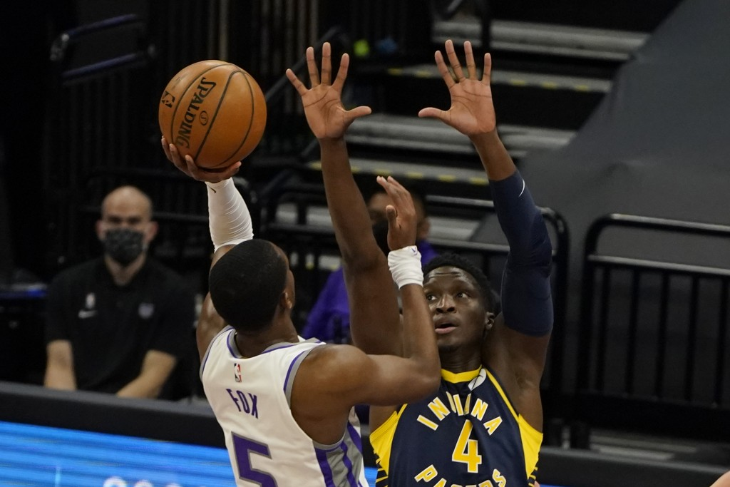 Sacramento Kings guard De'Aaron Fox, left, goes to the basket against Indiana Pacers guard Victor Oladipo during the first half of an NBA basketball g...