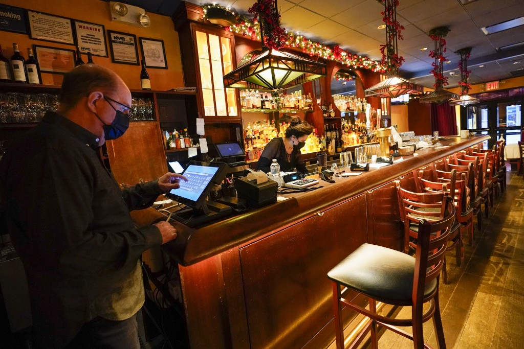 Steve Olsen, left, owner of the West Bank Café, sends a to-go order to the kitchen as Janet Momjian works at the bar in the empty restaurant, Saturday...