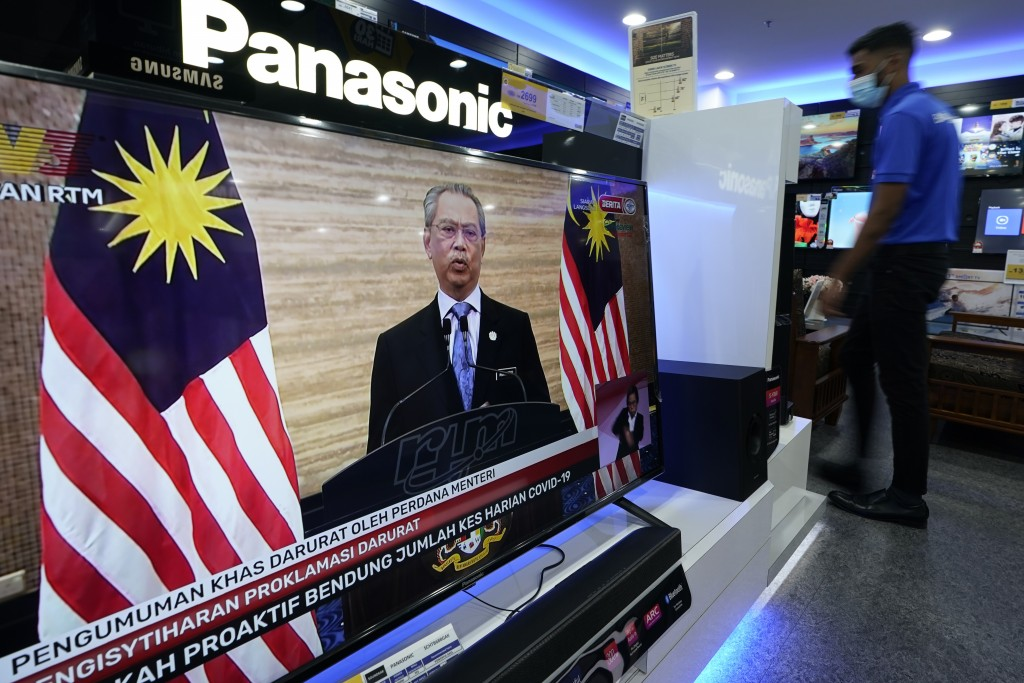 An electronic shop worker wearing a face mask walks near a television showing a live broadcast of Malaysian Prime Minister Muhyiddin Yassin at a shopp...