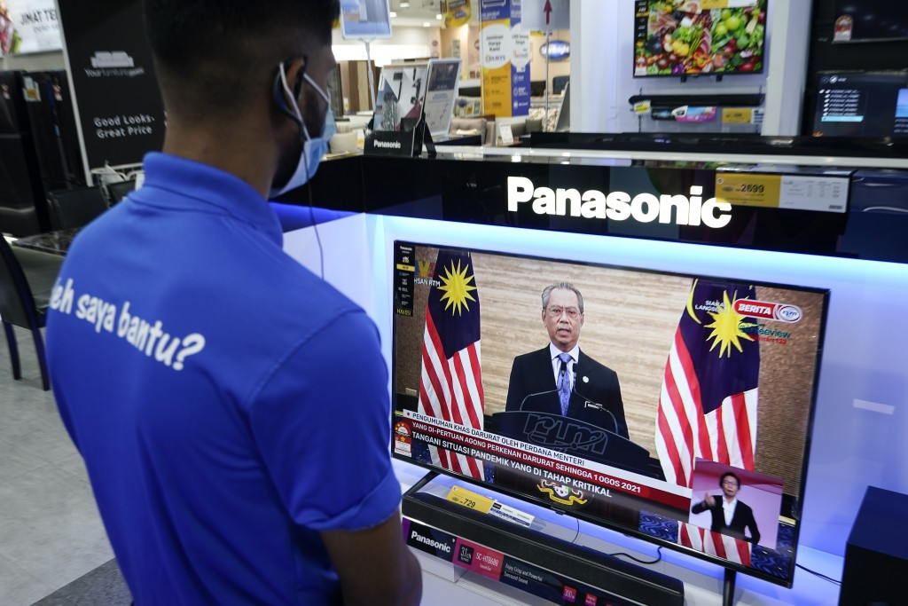 An electronic shop worker wearing a face mask watches a live broadcast of Malaysian Prime Minister Muhyiddin Yassin at a shopping outlet in Kuala Lump...