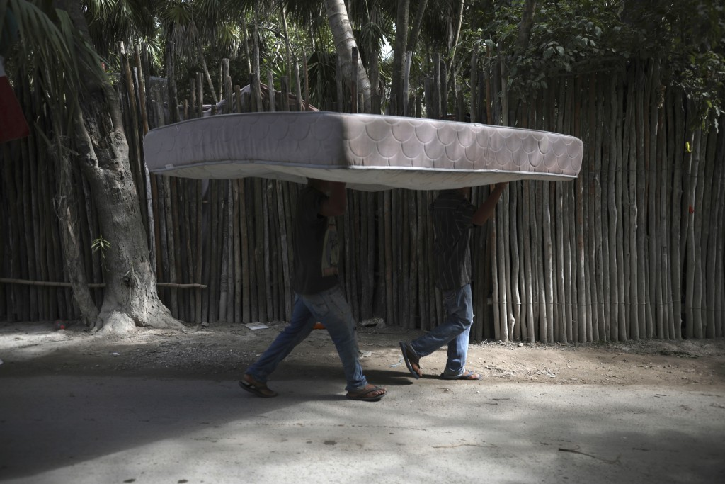 Workers carry a mattress from one hotel cabin to another in Tulum, Quintana Roo state, Mexico, Monday, Jan. 4, 2021. Tourism, which has been affected ...