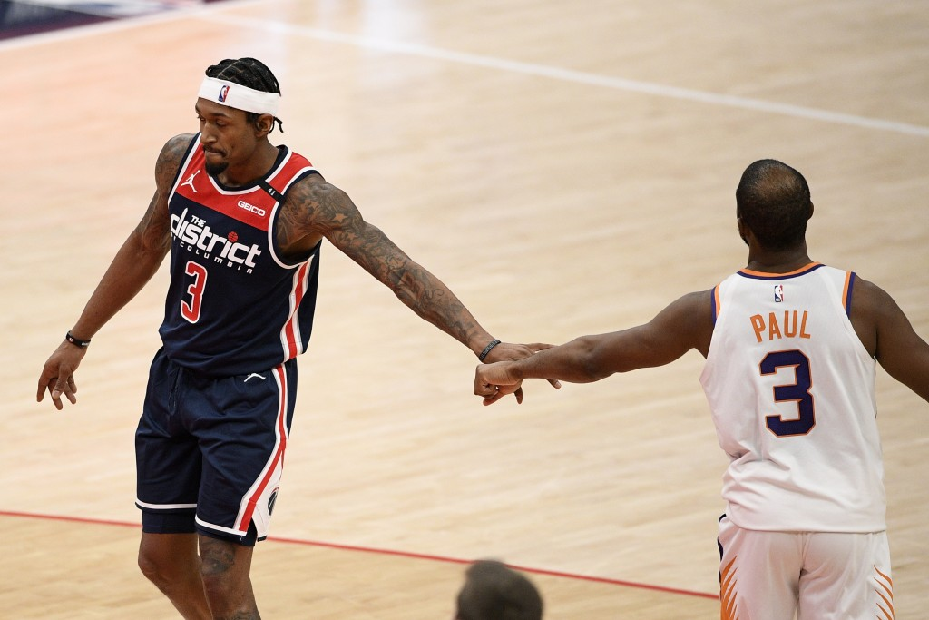 Washington Wizards guard Bradley Beal, left, and Phoenix Suns guard Chris Paul, right, tap hands during the second half of an NBA basketball game, Mon...