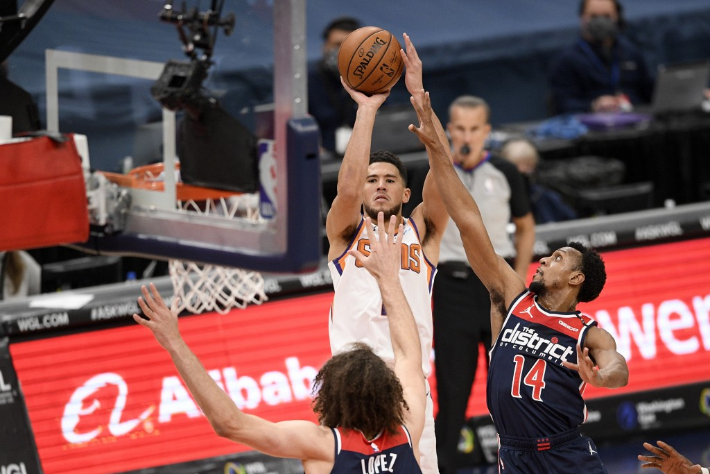 Phoenix Suns guard Devin Booker (1) shoots under pressure from Washington Wizards guard Ish Smith (14) and center Robin Lopez (15) during the first ha...