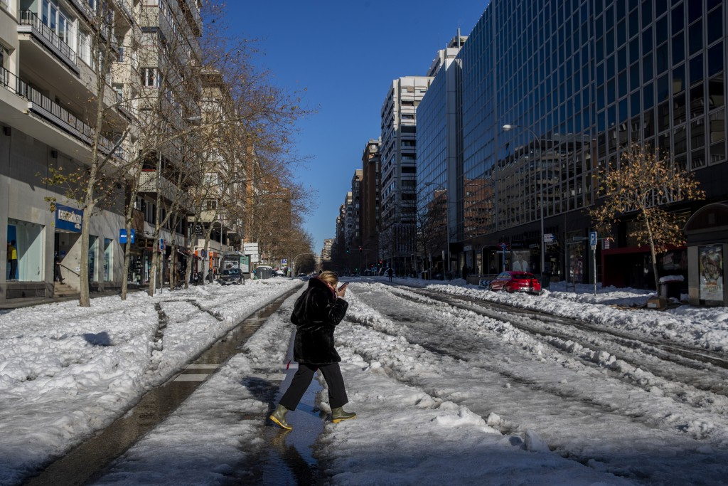 A woman walks through the snow in Madrid, Spain, Monday, Jan. 11, 2021. The Spanish capital is trying to get back on its feet after a 50-year record s...