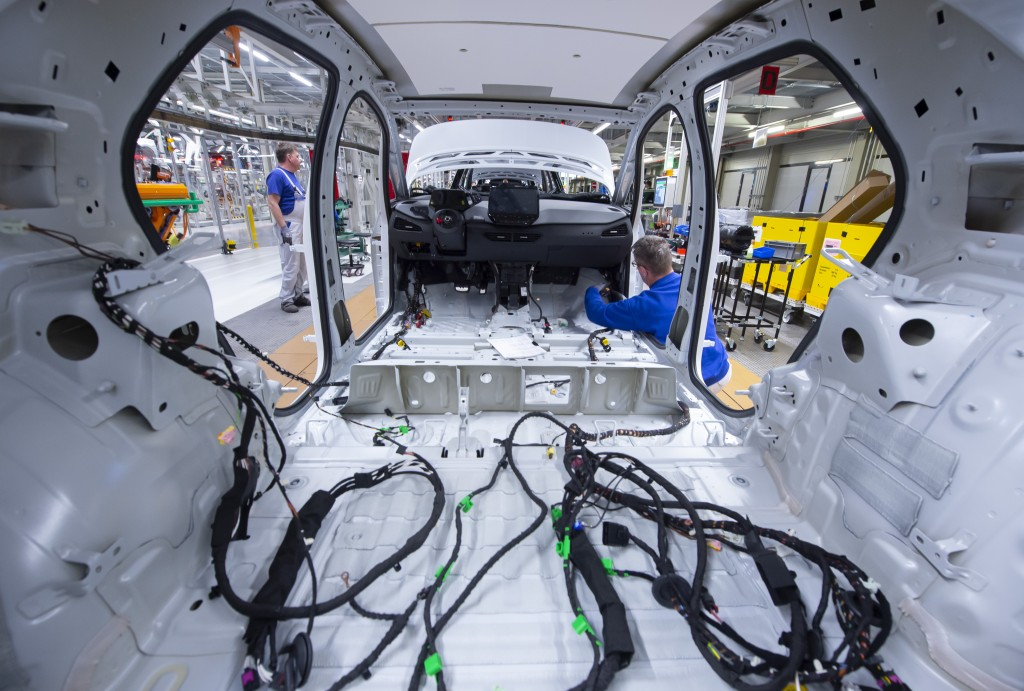FILE - In this Tuesday, Feb. 25, 2020 file photo, a worker completes an electric car ID.3 body at the assembly line, during a press tour at the plant ...