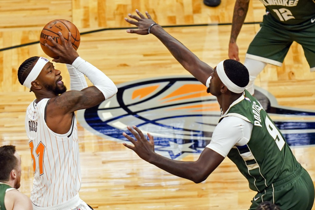 Orlando Magic guard Terrence Ross, left, takes a shot over Milwaukee Bucks center Bobby Portis (9) during the first half of an NBA basketball game, Mo...