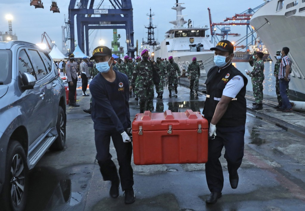 Members of the National Transportation Safety Committee carry a box containing the flight data recorder of Sriwijaya Air flight SJ-182 retrieved from ...