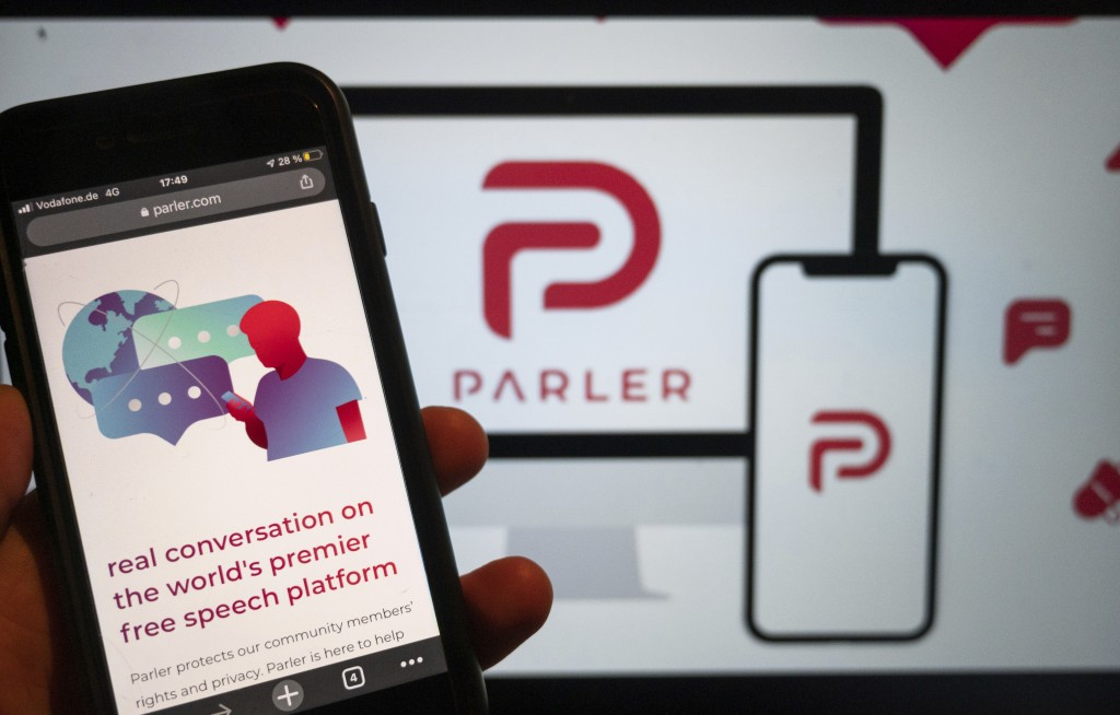 The website of the social media platform Parler is displayed in Berlin, Jan. 10, 2021. The platform's logo is on a screen in the background. The conse...