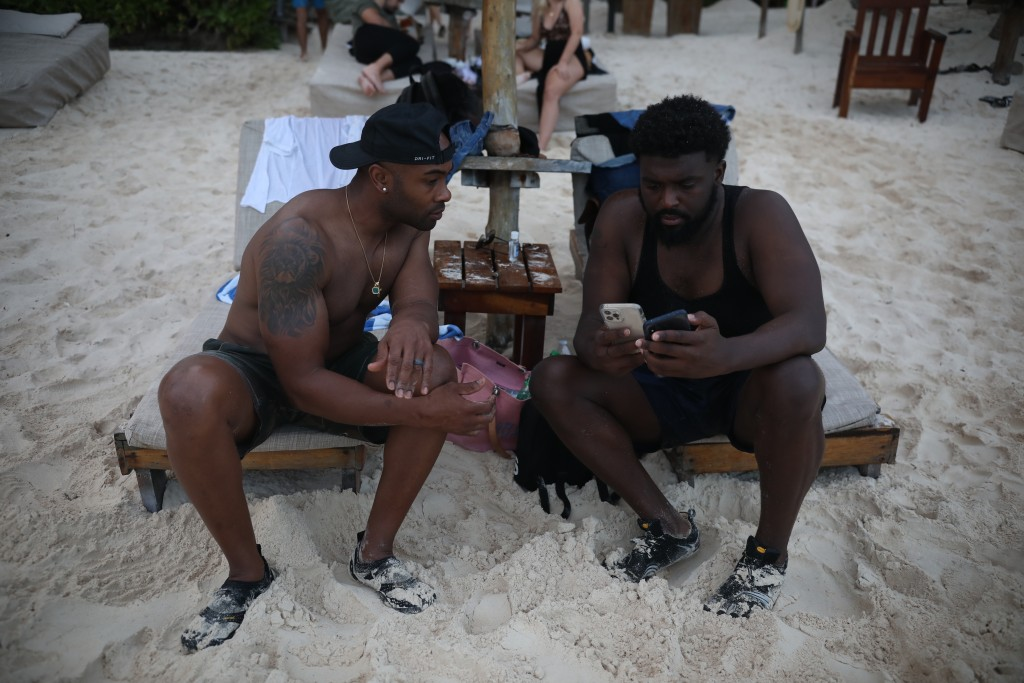 U.S. tourists Latron Evans, left, and Gearald Green, check their phones at a beach in Tulum, Quintana Roo state, Mexico, Monday, Jan. 4, 2021. The fri...