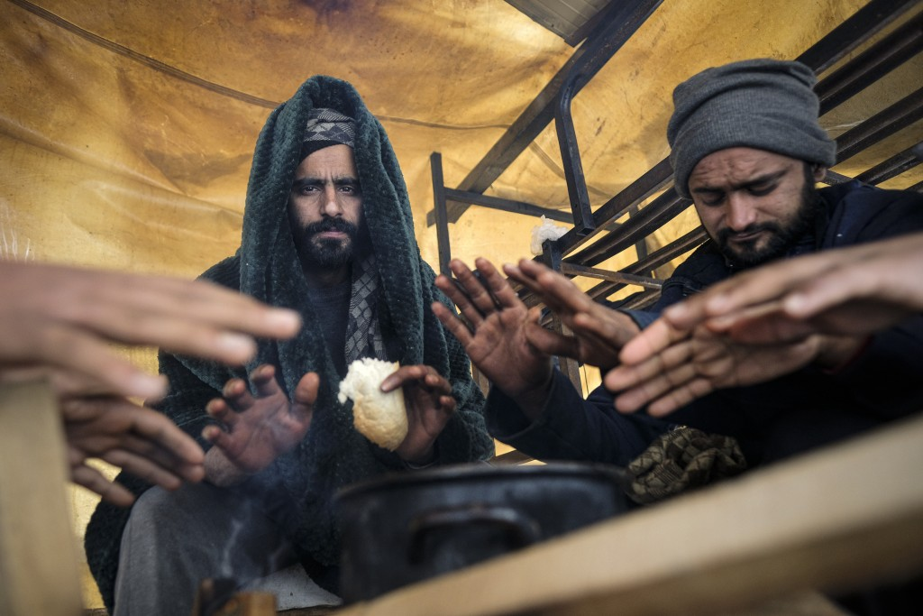 Migrants warm their hands above a fire at the Lipa camp, outside Bihac, Bosnia, Monday, Jan. 11, 2021. Aid workers say migrants staying at a camp in n...