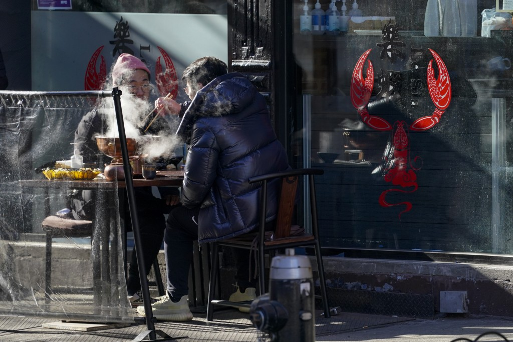 Steam rises from a dish as customers eat a meal on the sidewalk outside a restaurant, Sunday, Jan. 10, 2021, in the Hell's Kitchen neighborhood of New...