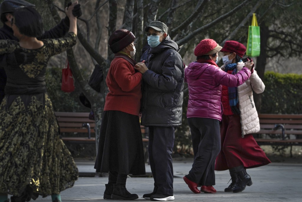 People wearing face masks to help curb the spread of the coronavirus enjoy a social dance at a public park in Beijing, Tuesday, Jan. 12, 2021. Lockdow...