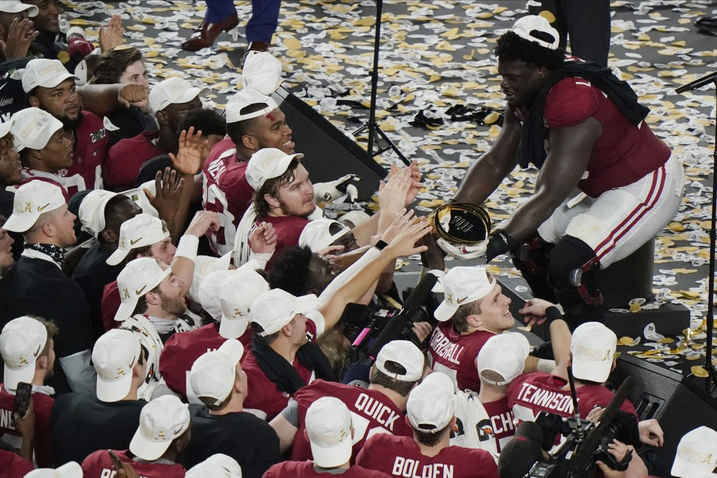 Alabama offensive lineman Alex Leatherwood holds the trophy for his teammates to touch after an NCAA College Football Playoff national championship ga...
