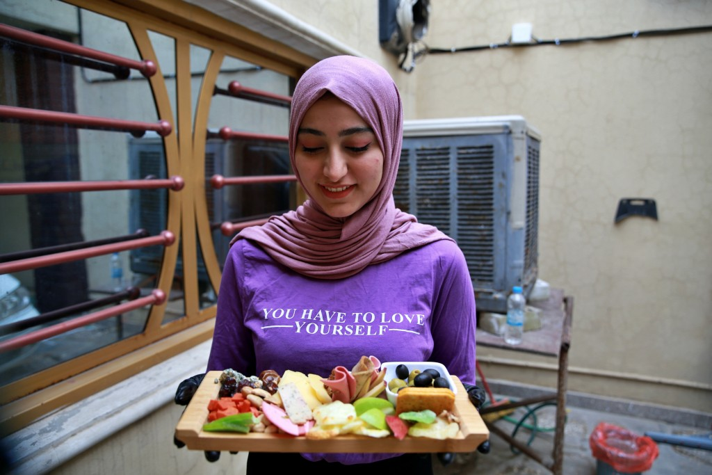 Fatima Ali shows her takeaway cheese-plate that she sells making a small but steady income, in Baghdad, Iraq, Saturday, Nov. 28, 2020. After Iraq impo...
