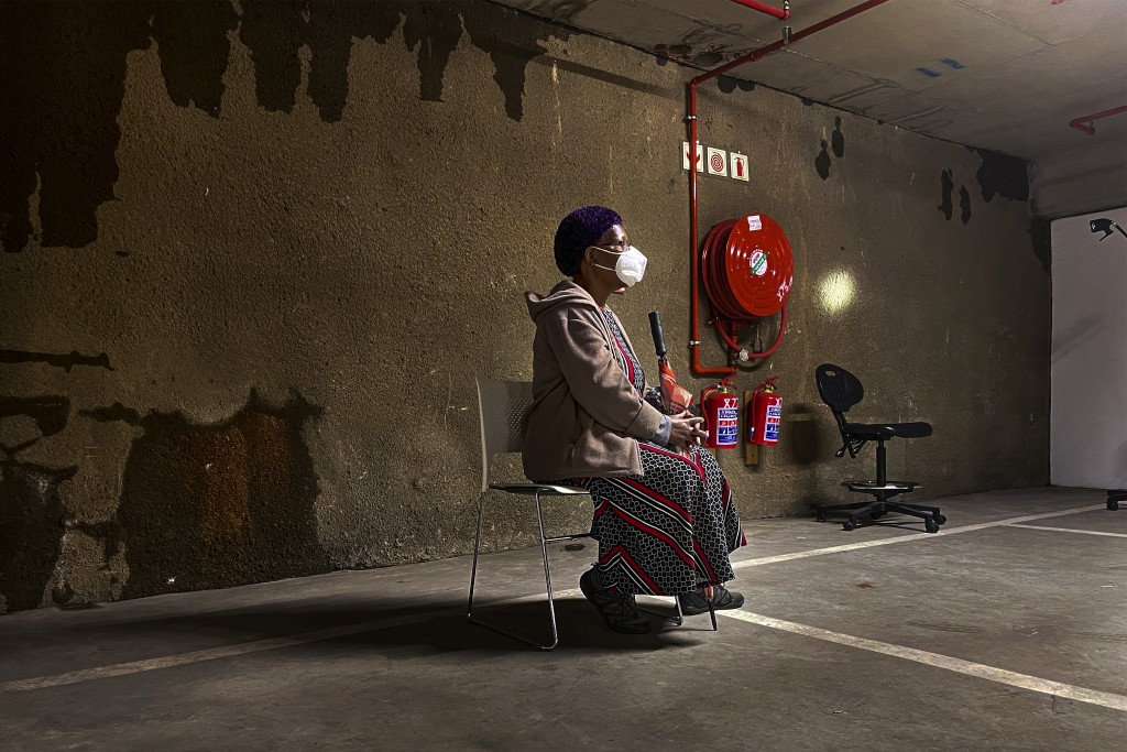 A lone woman waits to be tested for COVID-19 in the parking garage of a shopping mall in Johannesburg, South Africa, Monday Jan. 11, 2021. South Afric...