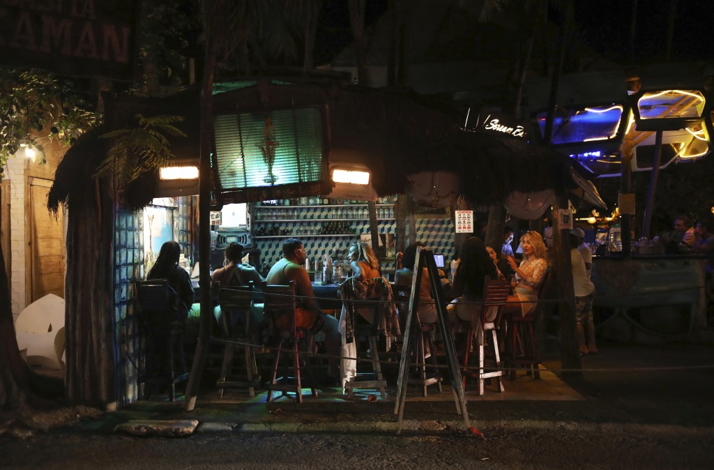 Tourists chat at a local bar on the main tourist strip of Tulum, Quintana Roo state, Mexico, Monday, Jan. 4, 2021. More U.S. tourists came to Quintana...