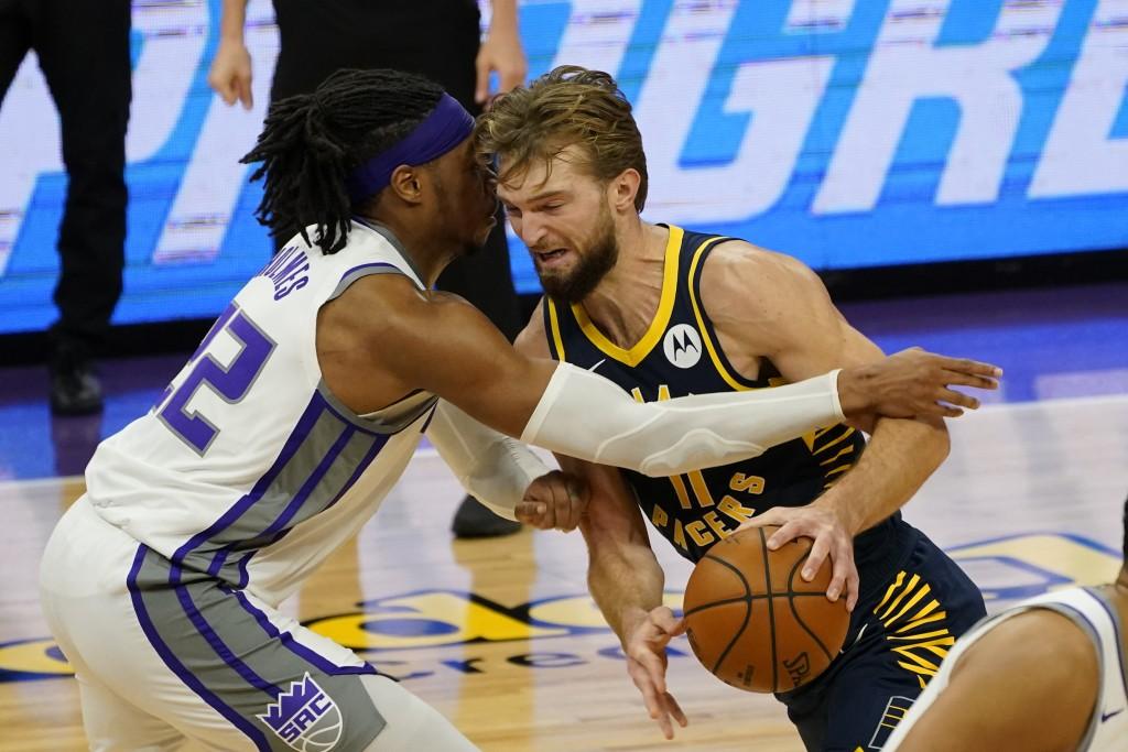 Sacramento Kings center Richaun Holmes, left, fouls Indiana Pacers forward Domantas Sabonis during the first half of an NBA basketball game in Sacrame...